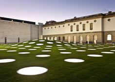Quase 200 clarabóias circulares dispostos em uma grade pelo gramado deixar a luz filtrar para dentro do salão de exposição, enquanto a colina artificial cria uma cúpula central.