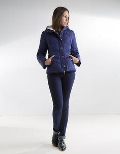 Plumífero corto azul de mujer con capucha, dos bolsillos laterales y cierre con cremallera y broches