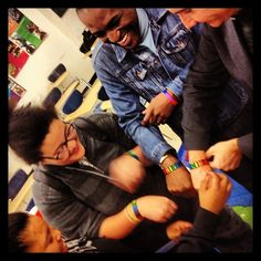 "Maurice Tomlinson and his husband Tom Decker receive PRIDE wristbands from GSA members at Collinsville High School in Illinois, while doing education outreach with filmmaker Micah Fink for ""The Abominable Crime,"" a feature-length documentary Fink made about violent homophobia in Jamaica. Image by education coordinator Amanda Ottoway."