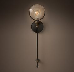 RH's Gaslight Lens Grand Sconce:Fusing past with present, our hand-forged sconce draws inspiration from historic lighting fixtures of the early 20th century. Designed by industrial blacksmith Jon Sarriugarte, convex glass lenses – originally used to protect gas flames from wind – are transformed into crystals that reflect and refract the light.