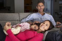 Hispanic Family On Sofa Watching TV And Eating Popcorn
