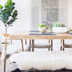Beautiful white on white Scandinavian style in this dining room featuring a white sliding screen, modern wood table, chairs, and bench with faux sheepskin rugs as throws (try Ikea for similar) and succulent centerpieces - Neutral Home Decor & Ideas