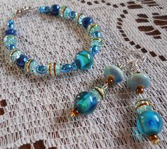 This stunningly pretty bracelet and earrings set are all handmade with Teal and Sky Blue Glass Beads, Gold Colored Czech Glass E-Beads and Gold-Rimmed Blue Crackle Glass Beads! Bracelet is connected by a Magnetic Clasp, Earrings with fish/french hook wire