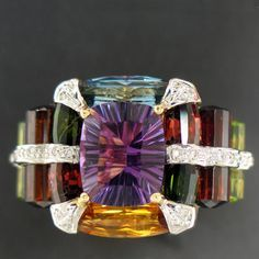 From the Bellari collection a ladies 18k Yellow Gold ladies ring. Amethyst center with multi colored gemstones & diamonds.