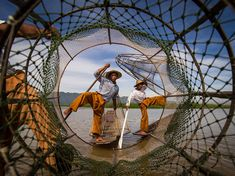 """Picture of men fishing in Myanmar - Photograph by Marco Marcone, National Geographic Your Shot  Your Shot member Marco Marcone snapped this artfully framed shot of fishermen balancing on small fishing vessels on Inle Lake in Myanmar. """"I was in a boat a little bit larger than that of the fishermen in the photo,"""" he writes. """"Honestly, they were just there for tourists … Anyway, I tried to do something new. I [hadn't] seen anyone before [put] the camera and himself inside the fishing net!"""""""