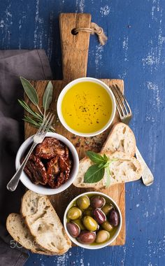 Mediterranean snacks set by sonyakamoz on PhotoDune. Olives, oil, herbs and sliced ciabatta bread on yellow rustic oak board over painted dark b. Bread Oil, Olive Oil Bread, Herb Bread, Ciabatta, Herb Recipes, Vegan Recipes, Olives, Fresco, Bread Shop