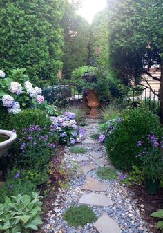 The mauve flowers, grey stones and green plants and bushes, create a very soothing and beautiful decor.