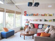 kid-friendly home: living room with book wall made from nine ikea ribba ledges (3 levels) + chiang mai fabric pillow + west elm pillows + vintage finds