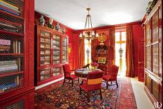A red paint that recalls bloodstone coats the paneling of a Houston house designed by Miles Redd. The chandelier is from Robert Kime, the George II drum table was found at Sotheby's, and the George III–style chairs were purchased at Christie's.