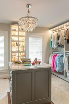 Chic walk-in closet features a Robert Abbey Bling Chandelier illuminating a gray closet island accented with wainscoting and topped with white marble.