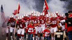 Nephews of deceased Nebraska punter Sam Foltz, Lane Foltz, left, and Max Foltz, right, join the team as they run onto the field, before an NCAA college football game against Fresno State in Lincoln, Neb.