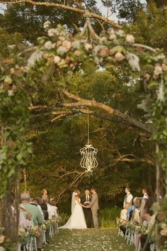 Ceremony with a floral arbor and chandelier