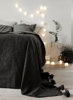 Love the romantic spirt of the dark grey bed and lights. Cosy bedroom.