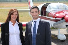 Man and woman in front of airplane ...  airfield, airplane, airport, aviation, aviator, black, business, capable, civil, commercial, craft, dress, female, firm, first professional, front, glad, glass, hair, land, love, male, own, owner, pilot, plane, posing, preparation, pride, profession, propellers, proud, shiny, shirt, silky, standing, tourism, white blouse, women, work