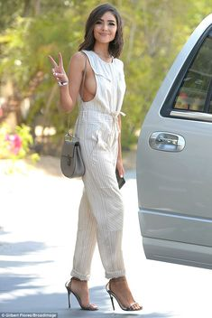 Flaunting it: Olivia Culpo, 24, looked stylish in a white pinstripe jumpsuit, which showed off her side boob