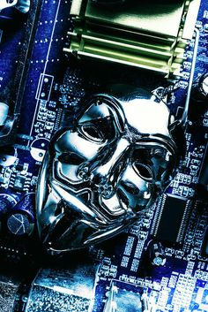 Shiny metal anonymous mask jewelry on computer motherboard circuit close-up, internet hacker concept by Jorgo Photography - Wall Art Gallery
