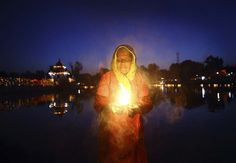 A devotee holds a lamp as she waits for sunrise to offer prayers during the Chhat festival in Kathmandu, Nepal Nepal People, Hindu India, Nepal Culture, Hindus, Big Flowers, World's Biggest, Incredible India, Photojournalism, Where To Go