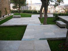 diseño de jardín con baldosas y parcelas de césped
