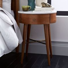 Inspired by mid-century design, our Penelope Nightstand stands on slim, tapered legs. Its marble top is wide enough for stacks of bedtime reading, while the rounded drawer is perfect for storing knickknacks.