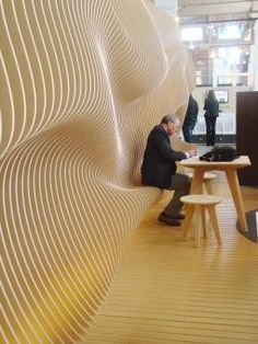 Furniture meets architecture. Profiled MDF sheets arranged to create visually striking installation with integrated seating.