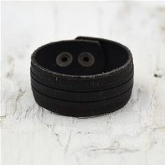 Mans leather cuff in black. A relaxed style with two stud fastening points.   ~Please note: Leather is a natural product, and as with all handmade items, there may be very minor imperfections  Dimensions:  Longest length: 23cm  Shortest length: 19cm