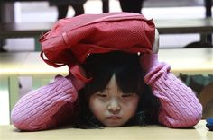 GALLERY: AP Top Photos of the Week. Pictured: A South Korean elementary school student covers her head with a schoolbag at an underground shelter after fleeing from her classroom during a drill against a possible air strike at Sohwa elementary school in Paju near the border with North Korea, South Korea, Tuesday, May 7, 2013. http://www.uticaod.com/features/x514216769/GALLERY-AP-Top-Photos-of-the-Week