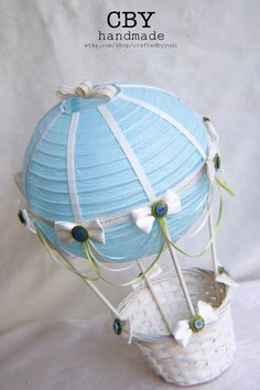 This beautifully handcrafted Hot Air Balloon centerpiece is made using a light blue paper lantern that has been adorned with ivory ribbons. It is decorated with light blue, light green and ivory ribbon draping and embellished with Ivory bows and accented with buttons to match. The