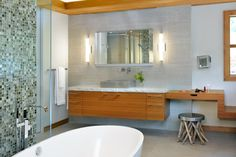 The waterfall bench connecting the makeup console and its supporting end embraces the idea of flowing water, much like that of Frank Lloyd Wright's famous Fallingwater house. Moreover, the wall-mounted faucets enhance the cascading effect of water.