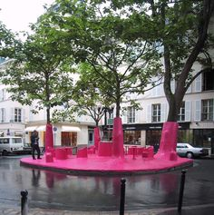 """PINK GHOST was implemented in Paris, in 2002, with """"a rose-coloured resin wraped around four trees and a street lamp up to 2m50 covering also the square's total surface."""" The exterior urban place thus became """"an (interior) exterior lounge and was suddenly questioning the status of the public space in the city."""" See http://www.peripheriques-architectes.com/pink-ghost"""