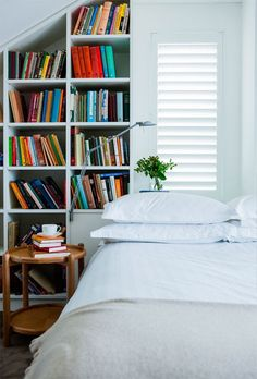 Clean white linens, a plant, and some books.