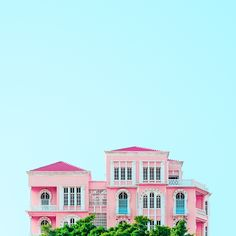A traditional Lebanese house against painted pink against a bright blue sky in Beirut.