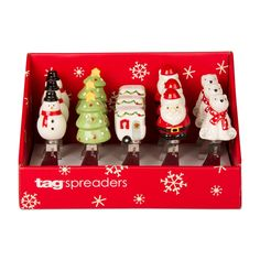 Christmas spreaders (5 total) by Tag (inscribed on blade). Earthenware?  Spreaders include: 1) snowman in black hat, red scarf; 2) Christmas tree w/ yellow star on top; 3) camper decorated w/ garland, red curtains, and door wreath; 4) Santa; 5) sitting polar bear in red&white scarf