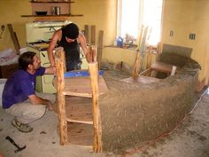 Building the kitchen island with cob, plywood, and pole branches