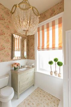Designer Lauren Messina brightens up the room with an elegant chandelier. The pretty floral wallpaper ties the colors in the room together.