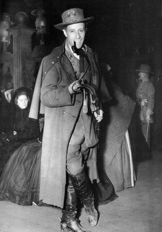 """"""" A pipe-smoking Leslie Howard in change #3, the Confederate major's butternut uniform, hat, overcoat and boots with spurs that Ashley wears to come home for Christmas (price $150). Sitting behind him..."""