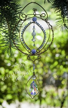 "This Sun Catcher has a quiet elegance and simplicity about it. It has beautiful blue crystal beads wrapped around the copper wire frame and a lovely drop pattern in center.  Suspended at base is a multifaceted crystal suspended with love, wire and beads. size 5 1/2"" x 10"" newmoonelements.blogspot.com"