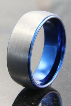 Mens brushed tungsten carbide wedding band with blue interior. This wedding band comes in 8mm in width. I love this silver and blue mens ring!