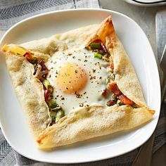 "Crepe-Framed Eggs with Asparagus Hash: The ""windows"" on this oven-baked brunch dish reveal a filling of chopped asparagus and pancetta, Gruyère and a sunny egg. Recipe: http://www.midwestliving.com/recipe/crepe-framed-eggs-with-asparagus-hash/"