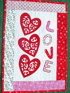 This quilted wall hanging has three red hearts with a decorative scroll design appliqued onto a light white and pink background. The center