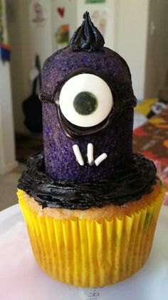 Purple minion cupcakes. Made with half Twinkie and sprayed with Wilton Purple Color Mist food color spray & Wilton monster eye candies and white sprinkles for teeth. Black gel icing to trace goggles and make frown for sprinkles to stick.