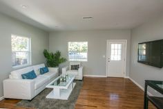 The look of this living room is just so clean & welcoming. White couch with blue throw pillows, white coffee table, light walls, and the beautiful hardwood floors bring it all together. #RealEstate #HouseFlipping #Bright #Light #Relaxing  www.verono.com/nassau