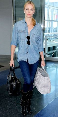 Theron departed from JFK airport in a denim-on-denim ensemble accessorized with a pair of leather totes and buckled boots.