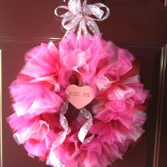 """Tulle Valentine Wreath.  I made this after seeing a similar one on Pinterest. I used a12"""" wreath form and 3 different colors of 6"""" tulle, hot pink, dark red and light pink.  The directions for the wreath I copied from suggested tying two 14"""" pieces of tulle around the form for each knot, so that's what did.  I attached some ribbon, a bow and a heart decoration and it's ready to hang on my front door!"""