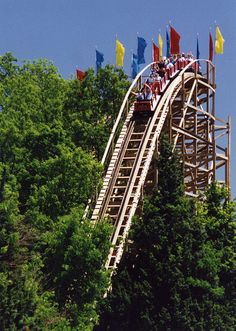 """The Raven    Features: 120-foot tunnel, 85-foot and 61-foot drops, sharp turn over Lake Rudolph and a double-banked """"s"""" curve at the bottom of second hill. Takes its name from Edgar Allan Poe's poem """"The Raven"""" and features sudden drops and turns which mimic the flight of a raven. From 2000 to 2003, The Raven was voted the world's """"Best Wooden Roller Coaster.""""   Located in Santa Claus, IN"""