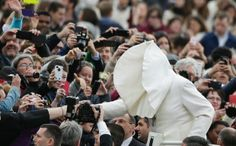 A gust of wind blows Pope Francis's mantle as he arrives to lead his Wednesday general audience in St Peter's square at the Vatican.