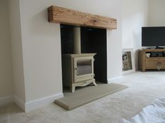 Chesneys wood burning stove with a stone hearth and oak beam. The Chesneys stove is a Beaumont 5 in cream.