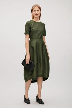 Made from a lightly textured blend of silk and cotton, this dress comes in and the waist and flares towards a cocoon-shaped skirt. It is completed with neat short sleeves, inseam pockets and is a hidden zip fastening along the back.