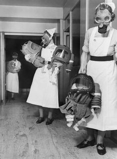 Appears to be nurses in gas masks taking their infant charges down to a bomb shelter.