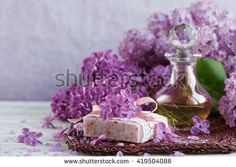 SPA concept: composition of spa treatment with natural sea salt,  aromatic oil and lilac flowers on white wooden background
