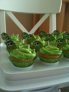 Dinosaur cupcakes. Yellow cake, mango buttercream frosting (http://www.holycowvegan.net/2009/11/mango-cupcakes-with-mango-buttercream.html) - I didn't go vegan and used butter; printed liner and dino head were from a Wilton's kit. I skipped the kit's candy spines and used sugar cookies instead - green-tinted, and hand-cut into triangles.